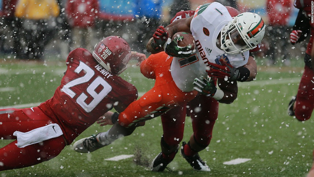 Snow falls in the ironically named Sun Bowl as Miami running back Mark Walton dives for a touchdown on Saturday, December 26. Washington State won the game 20-14 in El Paso, Texas.