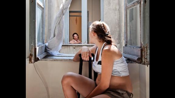 Carla talks to a neighbor at the window.