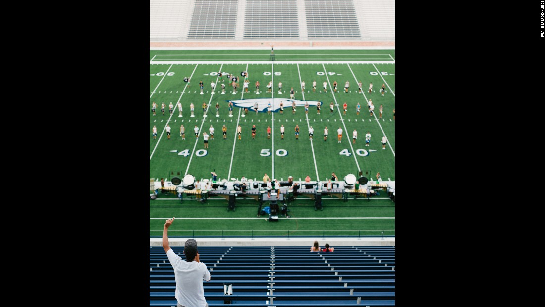 A staff member instructs the Cavaliers Drum & Bugle Corps from the upper deck of a stadium.