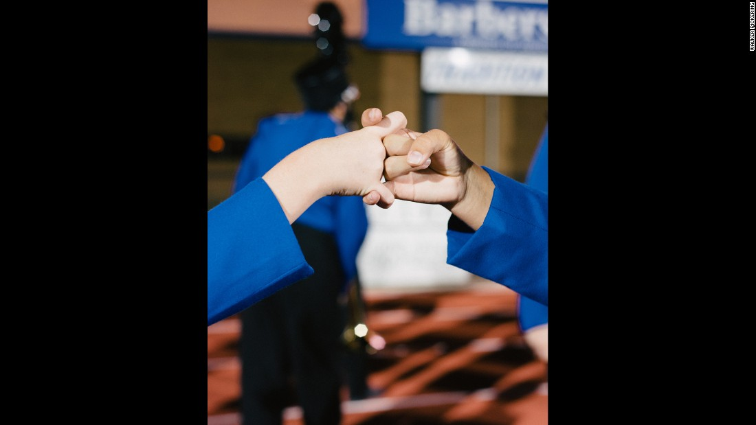 "Flute players from the Barbers Hill High School Marching Band perform the ""flute handshake"" before a performance."