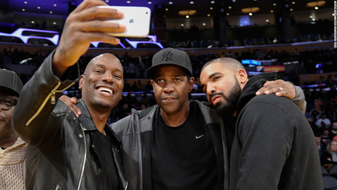 Actor and singer Tyrese Gibson takes a selfie with actor Denzel Washington, center, and rapper Drake during a Los Angeles Lakers basketball game on Wednesday, December 23.