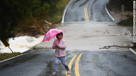 A girl walks near a flooded street in Austin, Texas, on October 24, 2015. Torrential rains created transit mayhem in the US state of Texas on October 24, including a train derailment and scores of canceled flights at one of the nation's busiest airports. AFP PHOTO/JEWEL SAMAD        (Photo credit should read JEWEL SAMAD/AFP/Getty Images)