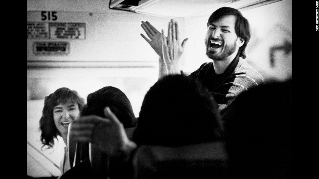 "Jobs returns from an employee picnic in 1987. ""Although Steve could be extremely rude, critical and even vindictive, he also was incredibly joyful most of the time, with an infectious grin and energy that was irresistible,"" Menuez said. ""Still, I did not observe too many of the unrestrained moments of hilarity as shown here, while Steve was riding an old rented school bus with the company employees."""