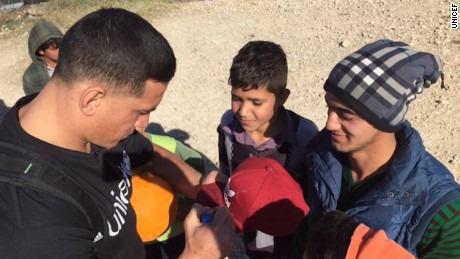 New Zealand rugby star Sonny Bill Williams signs a cap for a Syrian teenager at a refugee camp in Lebanon.