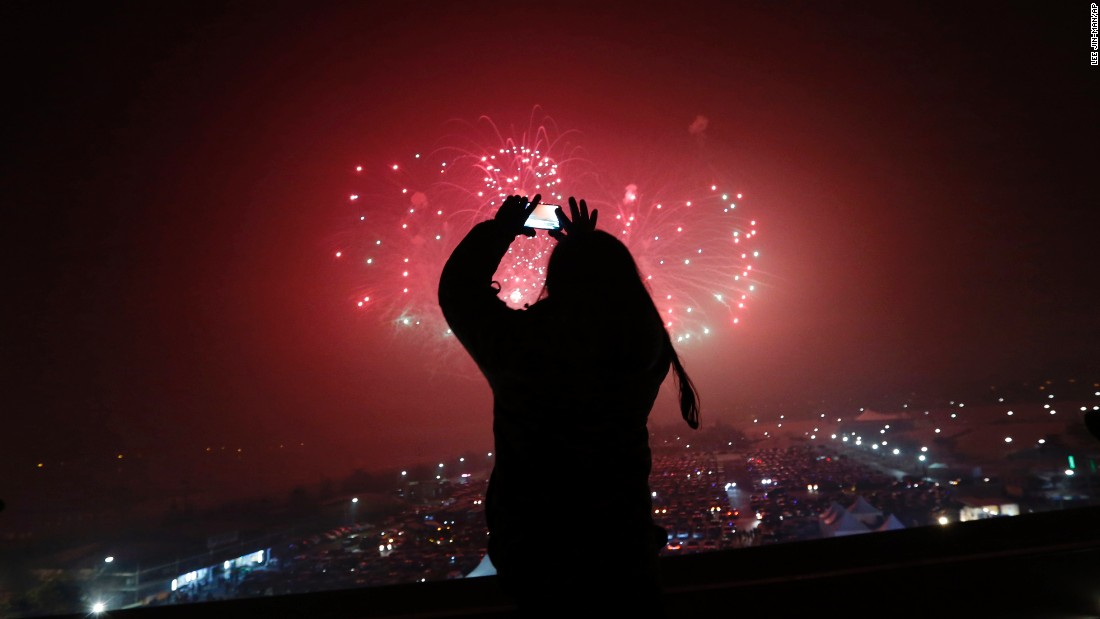 A woman takes a picture of fireworks while celebrating the new year in Paju, South Korea.