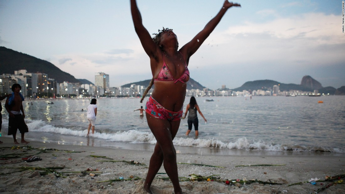 A reveler tosses rice in the air on Copacabana beach in Rio de Janeiro, Brazil.