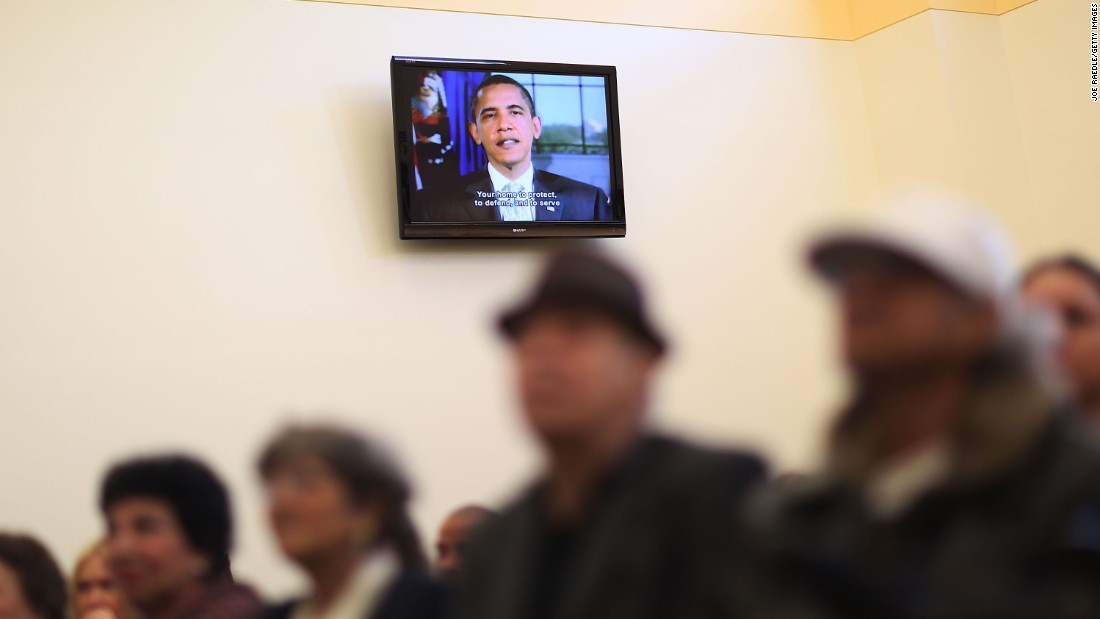 President Barack Obama is seen on a television screen congratulating people in Miami who had just been sworn in as naturalized U.S. citizens on Tuesday, December 29.