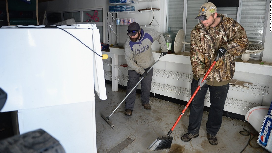 Matt Gerling, left, and Shane Menetzke clean debris from the concession stand of the Pacific Youth Assocation sports complex on January 1 in Pacific, Missouri.
