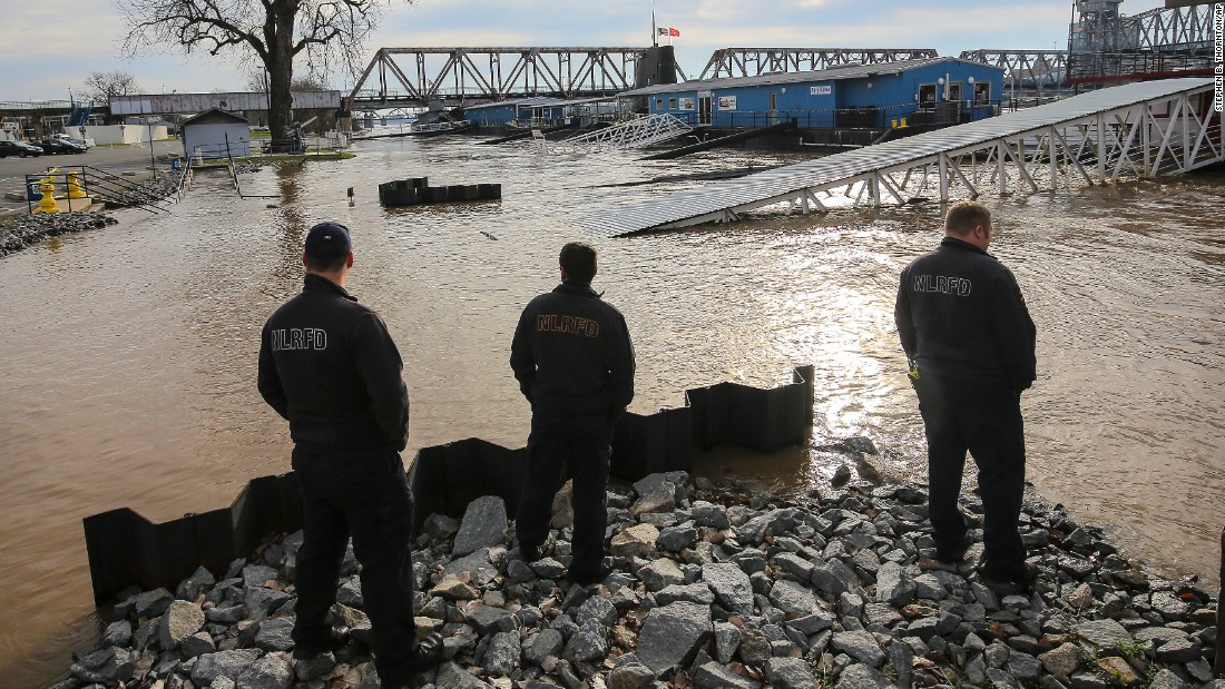 North Little Rock, Arkansas, firefighters look at the Arkansas River as it threatens a parking lot on January 1.