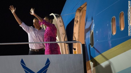 President Barack Obama and first lady Michelle Obama wave before boarding Air Force One at Joint Base Pearl Harbor-Hickam in Honolulu on January 2, 2016.