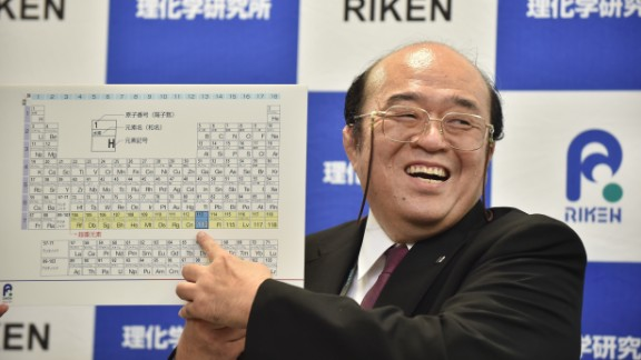 Kosuke Morita, the leader of the Riken team, smiles as he points to a board displaying the new atomic element 113 during a press conference in Wako, Saitama prefecture on December 31, 2015.  A Japanese research team has received naming rights for new atomic element 113, the first on the periodic chart to be named by Asian scientists, the team's institute said December 31. Japan's Riken Institute said a team led by Kosuke Morita was awarded the rights from global scientific bodies -- the International Union of Pure and Applied Chemistry (IUPAC) and the International Union of Pure and Applied Physics (IUPAP) -- after successfully creating the new synthetic element three times from 2004 to 2012.    AFP PHOTO / KAZUHIRO NOGI / AFP / KAZUHIRO NOGI        (Photo credit should read KAZUHIRO NOGI/AFP/Getty Images)