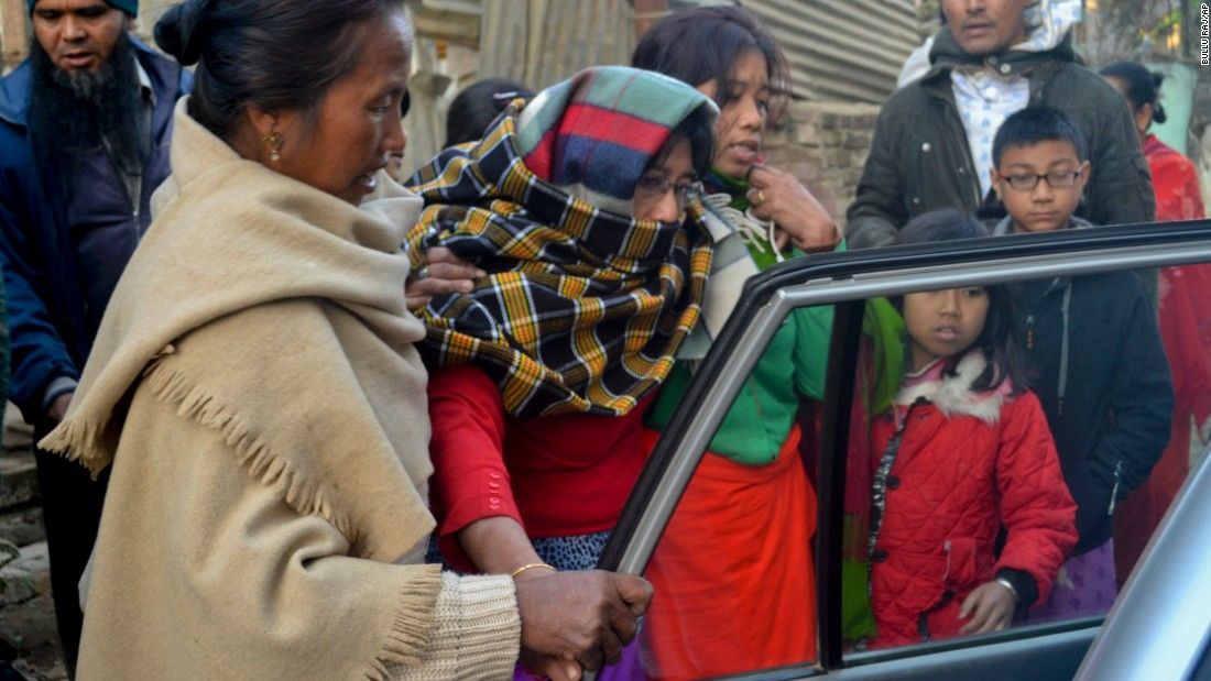An injured woman is helped into a car on her way to a hospital in Imphal on January 4.