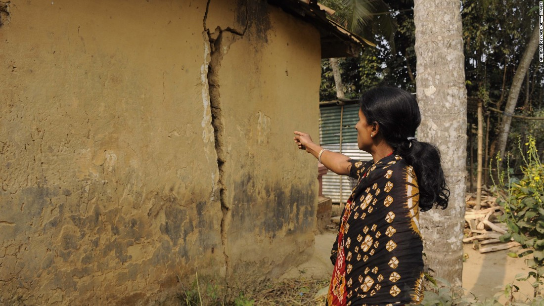 A woman points to a crack in a mud house jolted by the earthquake in the Malaynagar village, on the outskirts of Agartala.