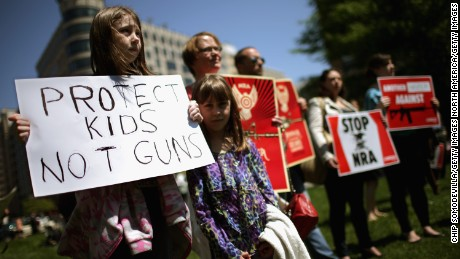 WASHINGTON, DC - APRIL 25:  Anti-gun violence demonstrators, including Rachel Ahrens (L), 13, Abby Ahrens, 8, and their mother Betty Ahrens hold signs condeming the National Rifle Association during a protest in McPhearson Square April 25, 2013 in Washington, DC. Angry with the U.S. Senate's failure to pass an expansion of background checks for people wanting to buy guns, the demonstrators attempted to deliver faux bank checks and crime scene photos to a handful of lobbying firms that represent the NRA.  (Photo by Chip Somodevilla/Getty Images)
