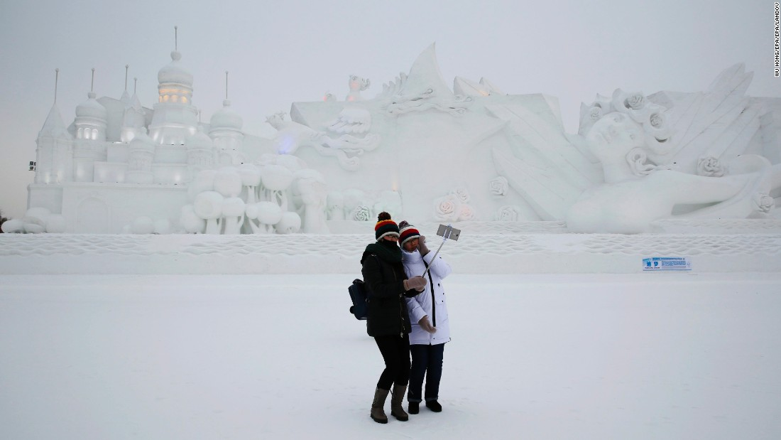 People take a selfie in front of a snow sculpture at an ice and snow festival in Harbin, China, on Tuesday, January 5.