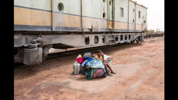 A child sits on luggage as he waits to board a passenger car.