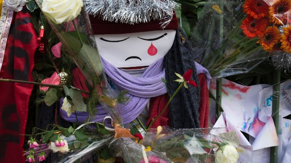 TOPSHOT - A doll crying is seen among flowers at a makeshift memorial in tribute to the victims of the Paris terror attacks, on January 4, 2016, outside the Bataclan concert hall in Paris, ahead of the one year anniversary of the jihadist attack on French satirical weekly newspaper Charlie Hebdo. Eight Charlie Hebdo staff were among the victims of the January 7, 2015 assault which brought millions of people onto France