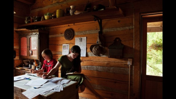 Iris and Roan, two homeschooled children in rural New York, do homework in 2012. They live on a family farm with their parents, who follow a nature-based learning method and believe their children would benefit more from spending their time within nature and at home rather than on a school bus and in a classroom, photographer Rachel Papo said. Papo spent time with about 15 homeschooled children over two years, and her photos will be published in a book this spring.