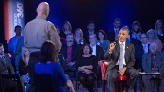 President Barack Obama, right, answers questions from Arizona Sheriff Paul Babeu, left standing, during a CNN televised town hall meeting at George Mason University in Fairfax, Va., Thursday, Jan. 7, 2016. Obama