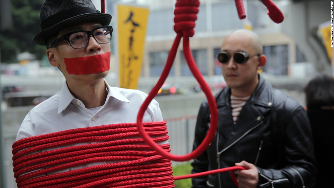 A protester is wrapped up with a rope made into a noose during a march calling for the release of missing booksellers from Hong Kong's Mighty Current publishing house on January 10, 2016.
