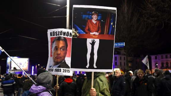 """Protesters in Leipzig hold aloft posters depicting German Chancellor Angela Merkel being groped and of Hungarian PM Viktor Orban, known for his anti-migrant stance. The latter reads """"Thanks"""" in Hungarian."""