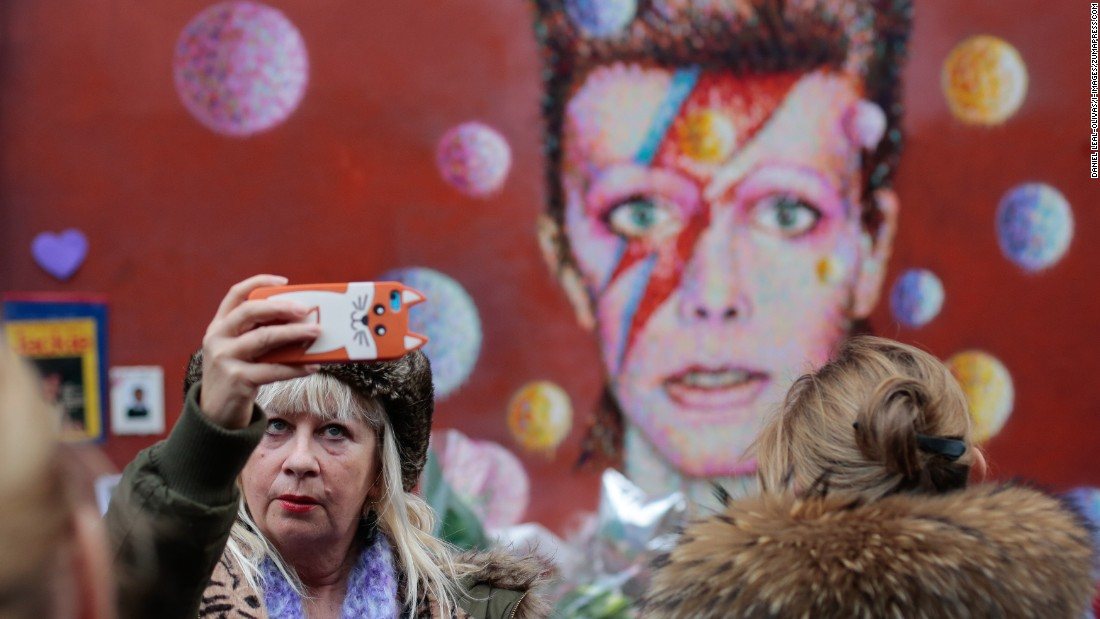 "A woman takes a selfie in front of a David Bowie mural in London on Tuesday, January 12. <a href=""http://www.cnn.com/2016/01/11/entertainment/david-bowie-thr-obit/index.html"" target=""_blank"">The rock legend died</a> January 10 at the age of 69."