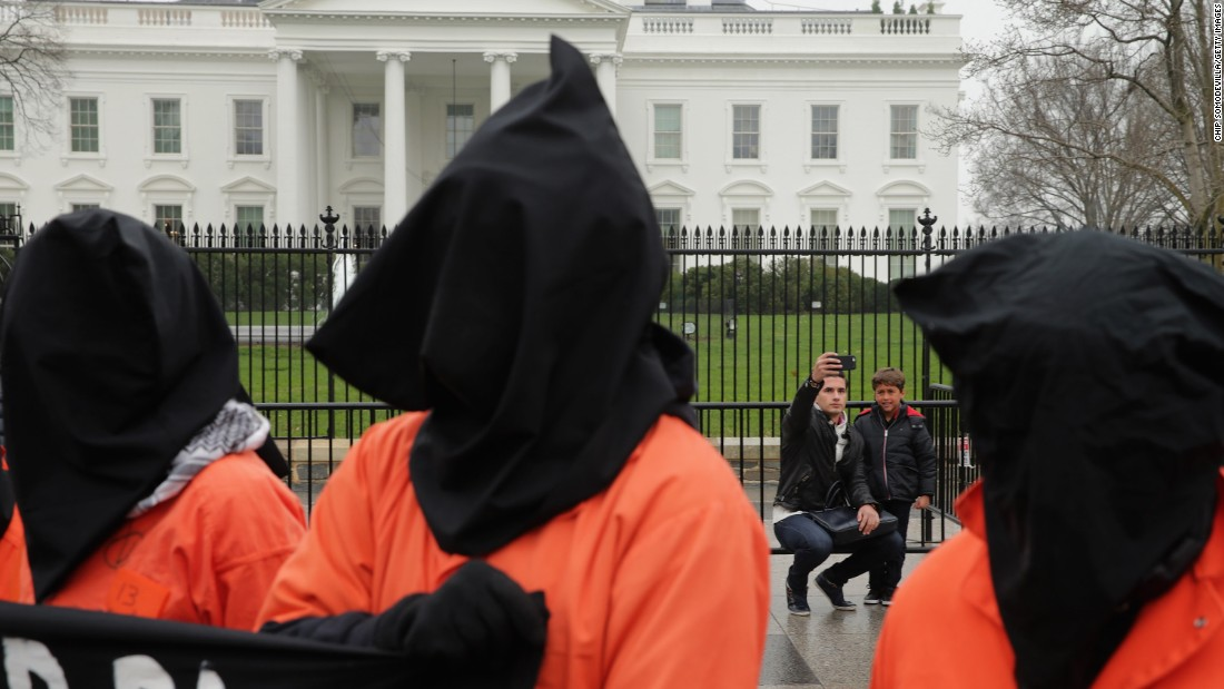 Tourists pose for a selfie in front of the White House as an anti-torture protest takes place near them in Washington on Friday, January 8.