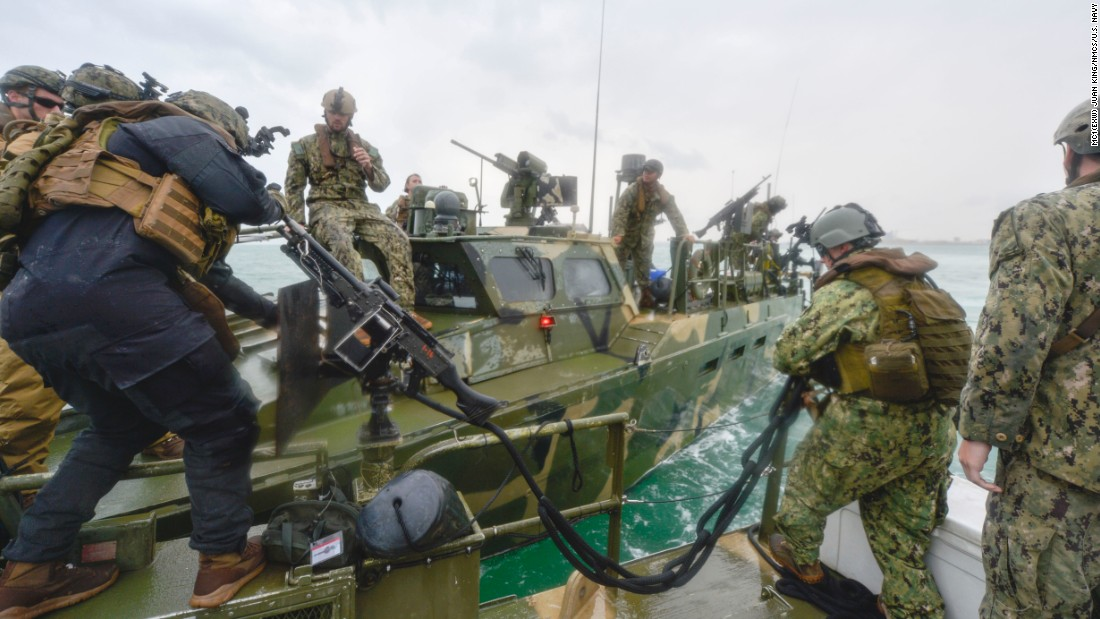 Sailors secure a towline to a riverine command boat during a training exercise.