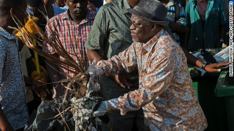 Tanzanian President John Magufuli joins a clean-up event outside the State House in Dar es Salaam on December 9, 2015 - Independence Day.