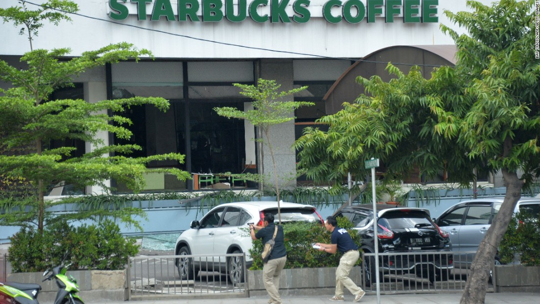Plainclothes police officers aim their guns at suspects outside a cafe after a series of blasts hit the center of Jakarta on January 14.