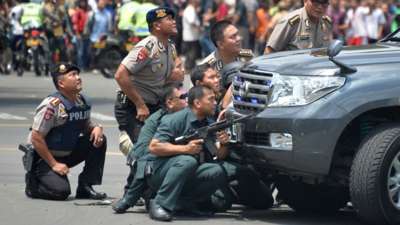 Indonesian police take position behind a vehicle as they pursue suspects after a series of blasts hit the center of Jakarta on January 14.