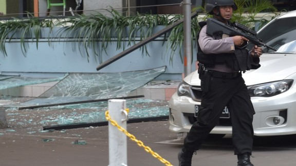 """An Indonesian anti-terror policeman walks next to the Starbucks cafe after several blasts and shootings in Jakarta on January 14, 2016.  Gunfire and explosions in the Indonesian capital Jakarta killed at least six people on January 14 in what the country's president dubbed """"acts of terror"""", with fears that militants were still on the run. Starbucks announced in a statement that the company was closing all of its Jakarta branches """"until further notice"""" after one of its stores in the Indonesian capital was hit by apparent suicide attacks.  / AFP/AFP/Getty Images"""