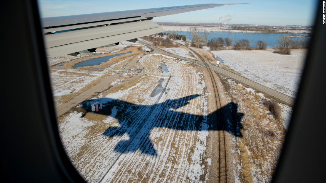 Air Force One casts a shadow over a snow-covered field as it approaches Bellevue, Nebraska, on Wednesday, January 13.
