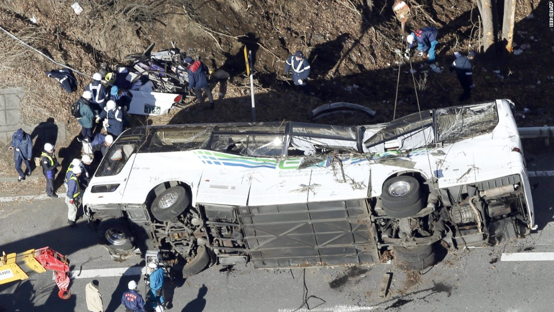 Investigators work near the damaged wreck after it was transferred by crane onto a road in Karuizawa, Nagano prefecture, central Japan Friday, Jan. 15, 2016.