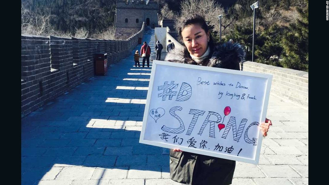 "Beijing resident Xu Jin poses with a sign saying ""#DStrong"" on the Great Wall, on the city's outskirts."