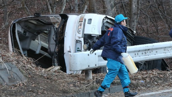 An investigator walks beside the bus wreckage on January 15, 2016. The tour bus veered off the road on the way to a ski resort in central Japan.