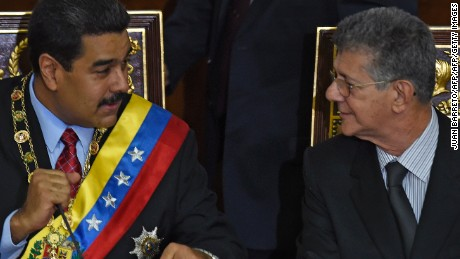 "Venezuelan President Nicolas Maduro (L) speaks with the president of the opposition controlled National Assembly, Henry Ramos Allup (R), during his annual report at the National Assembly in Caracas on January 15, 2016. Venezuela's President Nicolas Maduro decreed a two-month state of ""economic emergency"" Friday, seizing the initiative ahead of a key showdown in his standoff with the opposition in the oil-rich nation. Venezuela's economy contracted 4.5 percent in the first nine months of 2015, the central bank said Friday, the first official data in more than a year on the magnitude of the South American oil giant's recession. AFP PHOTO / JUAN BARRETO / AFP / JUAN BARRETO / AFP / JUAN BARRETO        (Photo credit should read JUAN BARRETO/AFP/Getty Images)"