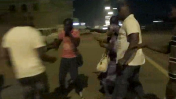 In this image taken from video from AP Television, plain-clothed policemen leading people away near the Splendid Hotel, Friday, Jan. 15, 2016, in Ouagadougou, Burkina Faso. The SITE Intelligence Group reports that an al-Qaida affiliate is claiming responsibility for the ongoing siege on an upscale hotel and cafe in Burkina Faso's capital where an unknown number of hostages are being held. (AP Television via AP)