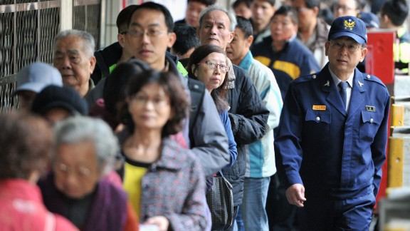 A police officer patrols a polling station as local residents line up at the Xindian district in Taipei.