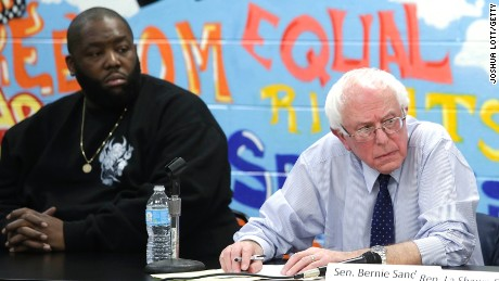 Rapper Killer Mike (left) listens as Bernie Sanders speaks during a roundtable meeting with local activist and community members December 23, 2015, in Chicago.