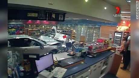 NS Slug: AUSTRALIA: GAS STATION CRASH, CAR MISSES WOMAN (STRONG!)  Synopsis: Car crashes into a gas station in Australia, narrowly missing a woman inside. The incident was caught on camera.  Keywords: AUSTRALIA GAS STATION ACCIDENT COLLISION CLOSE CALL