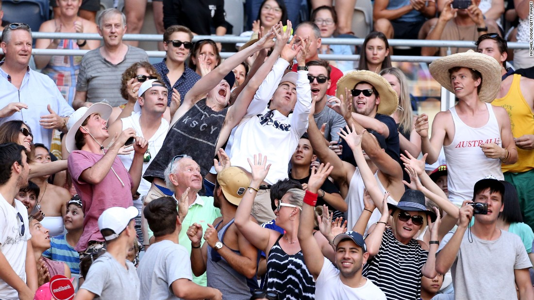 Fans attempt to catch a stray tennis ball during the match between Wozniacki and Putintseva.