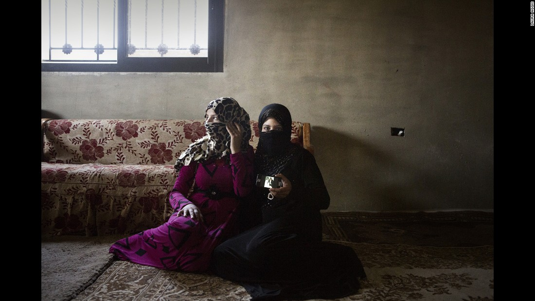 Houda, 14, and Nour, 13, show their wedding photos. They are sisters. Nour has already had a miscarriage.