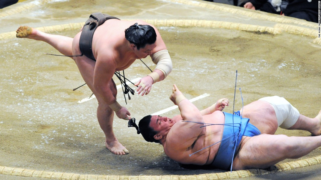 Hakuho throws Aoiyama to win a match at the New Year Grand Sumo Tournament in Tokyo on Thursday, January 14.