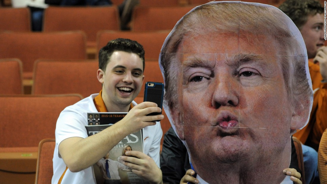 A basketball fan at the University of Texas takes a selfie with a Donald Trump cutout before a game on Tuesday, January 12. Celebrity heads have become a popular feature at many basketball games, with fans waving them to distract opposing free-throw shooters.