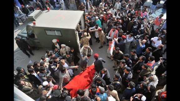 Rescue workers move an injured victim to an army ambulance.