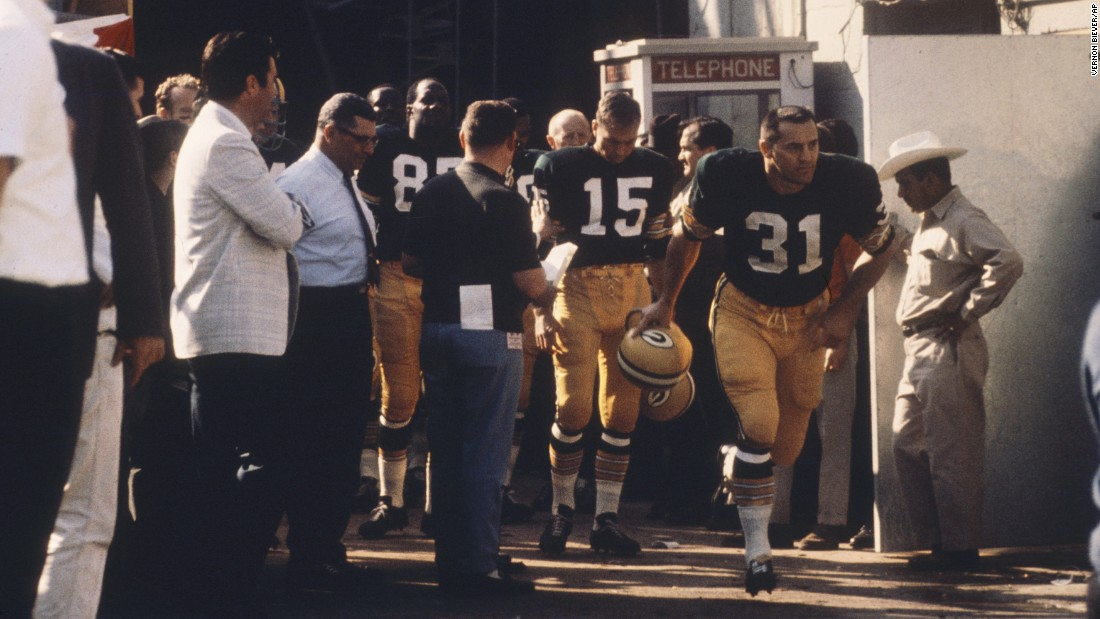 Packers fullback Jim Taylor (No. 31) leads a group of teammates out of a tunnel before the game. Behind him is quarterback Bart Starr (No. 15). Both are now in the Pro Football Hall of Fame.