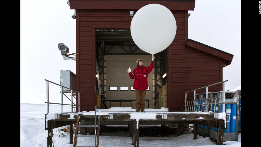 A researcher holds a weather balloon designed to collect climate data.