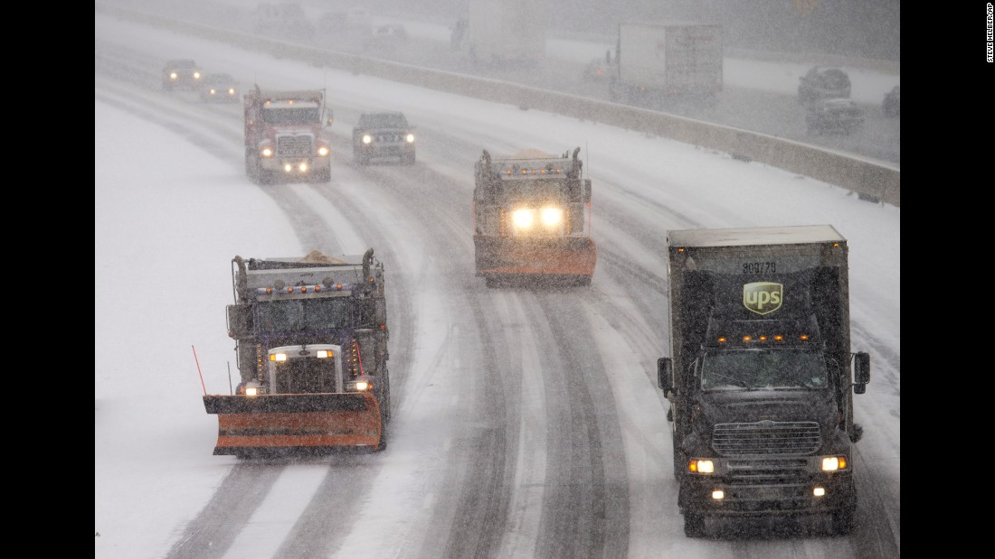 Snow plows make their way north along Interstate 95 as snow begins to fall in Ashland, Virginia, on January 22.