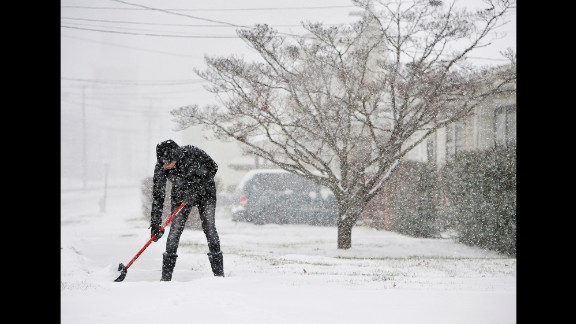 A woman in Lynchburg shovels the sidewalks in front of her house on January 22.
